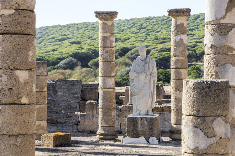Statue of Roman emperor Trajan in the ruins of Baelo Claudia, an ancient Roman town outside of Tarifa, near the village of Bolonia, in Andalusia, southern Spain Baelo Claudia Bolonia Spain Roman Ruins Ancient Ancient Civilization Architectural Column Architecture Art And Craft Built Structure Day History Human Representation Male Likeness Mountain No People Old Ruin Outdoors Sculpture Sky Statue Travel Destinations Tree