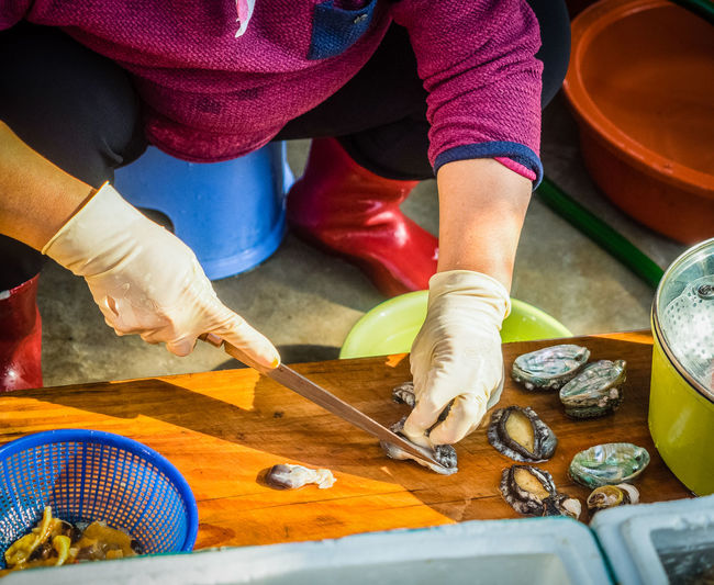 Low section of woman preparing clams on cutting board