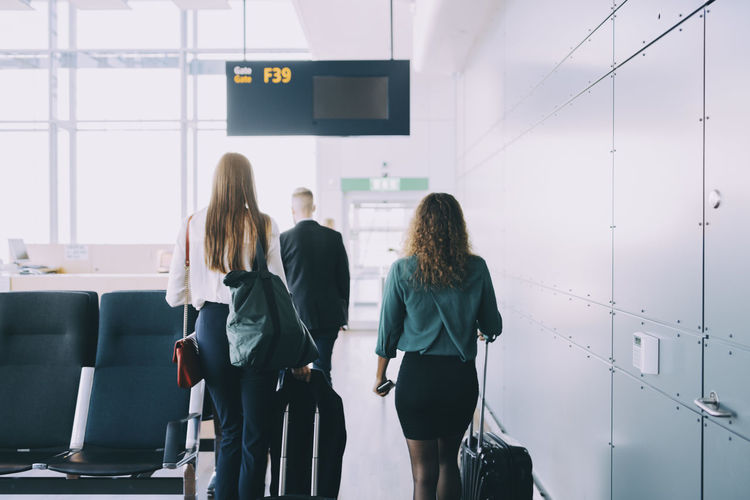 Rear view of woman standing at airport