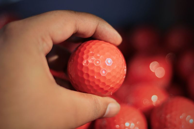 Close-Up Of Person Hand Holding Red Golf Ball