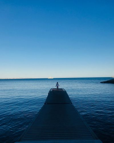 Mid Distance View Of Woman On Pier Over Sea Against Clear Sky