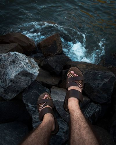 Low section of man sitting on rocky shore