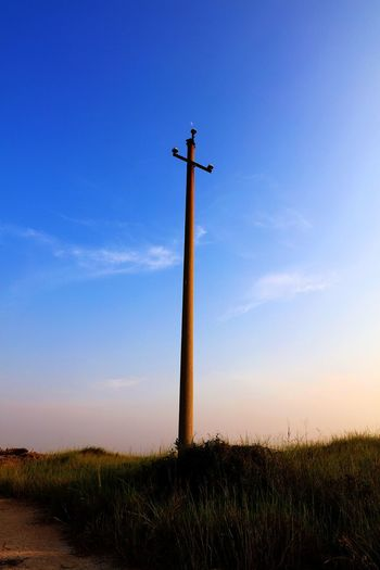 Low angle view of telephone pole on field against sky