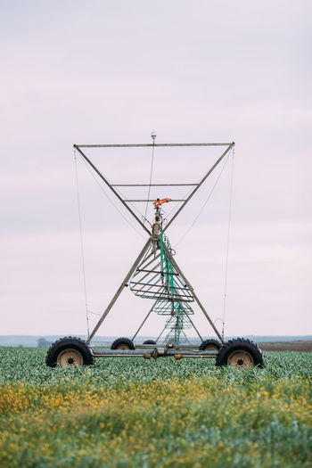 Irrigation Equipment Irrigation Irrigation System Agriculture Agricultural Field Farm Landscape Field Rural Scene Outdoors Day Green Color Sky Environment Nature Plant Land No People Corn Plantation Built Structure Transportation Technology Growth Grass