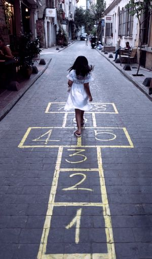Full length of girl playing hopscotch on road in city