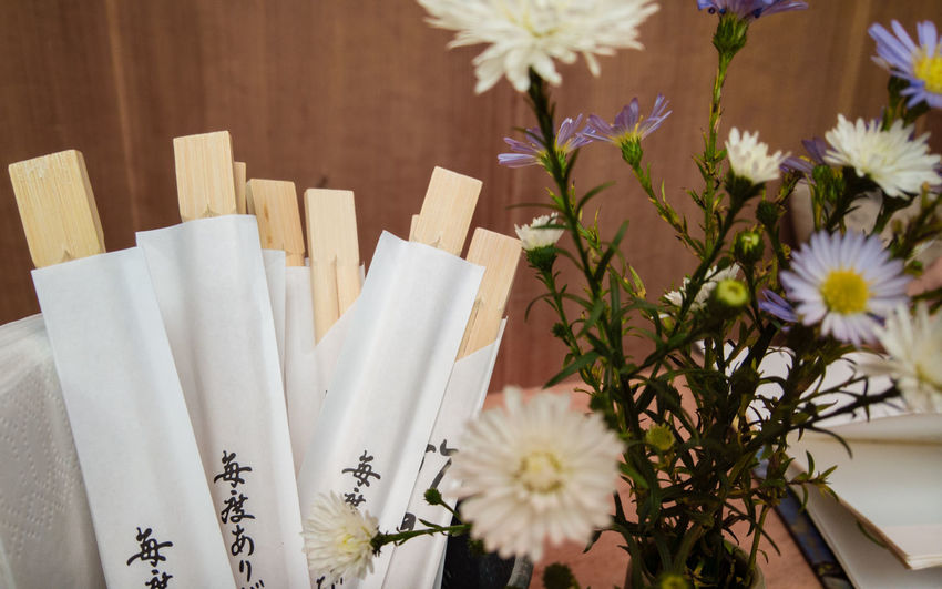 Close-up of flowers by chopsticks in packets on table