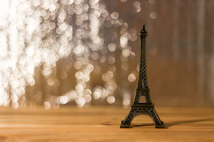 Close-up of replica eiffel tower on wooden table against light