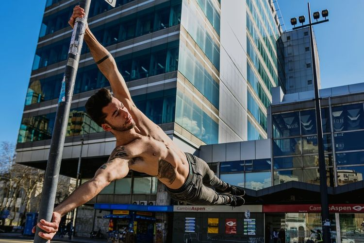 Low angle view of shirtless young man exercising against building in city