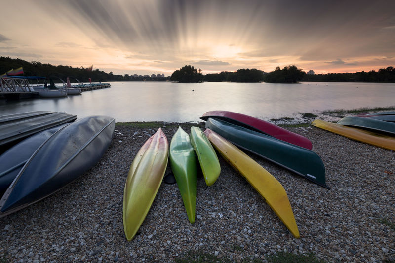 Long exposure shot of colorful kayaks at a lake. Adventure Beauty In Nature Canoe Day Kayaks Kayaks In Racks Lake Landscape Mountain Nature Nautical Vessel No People Outdoors People People Watching Reflection Sky Walking Around Water Waterfront