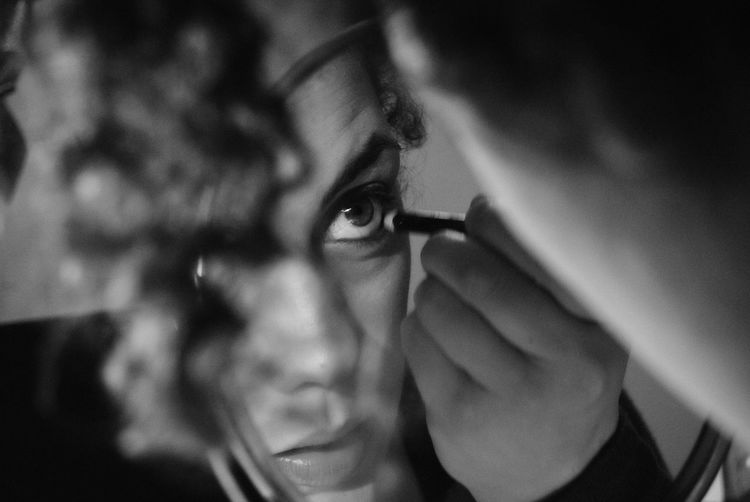 Close-up of woman applying make-up reflecting on mirror