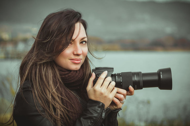 Portrait of beautiful woman holding camera