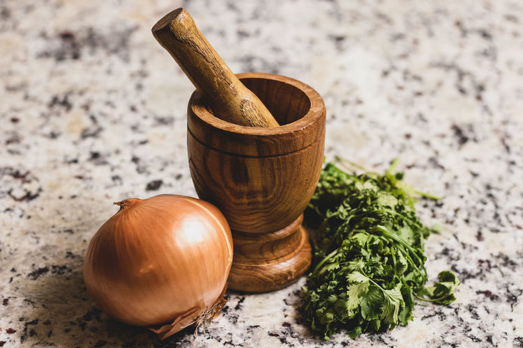 Still life image of wooden mortar and pestle, onion and cilantro.