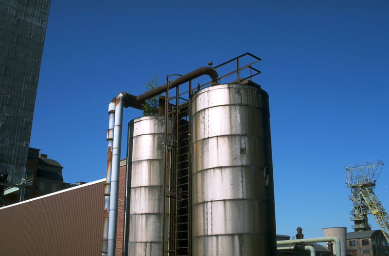 Low angle view of industrial building against blue sky
