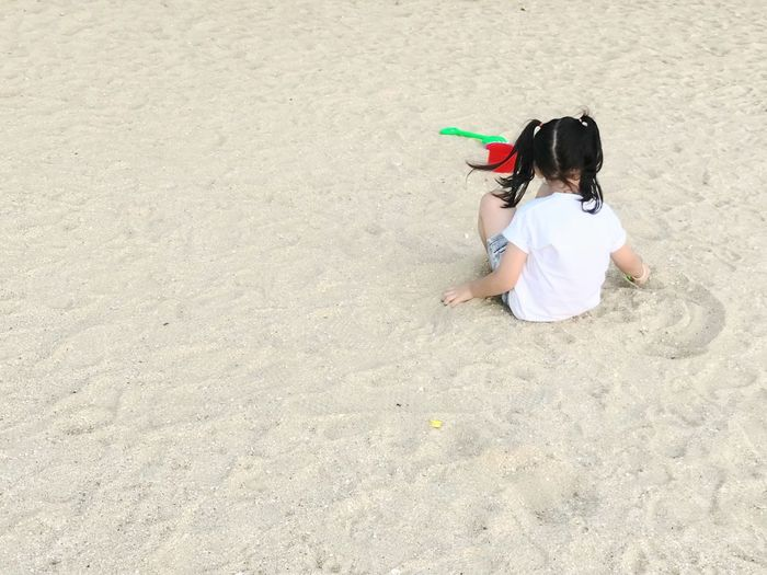 High angle view of girl with toy on beach