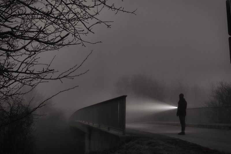 Man with flashlight standing on road at night