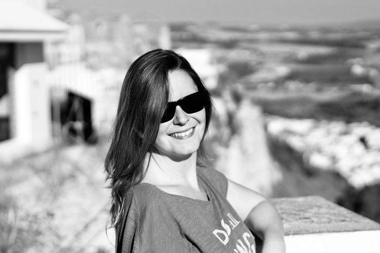 Portrait of smiling woman wearing sunglasses outdoors