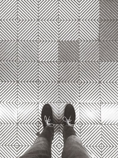 Low section of man standing on patterned floor