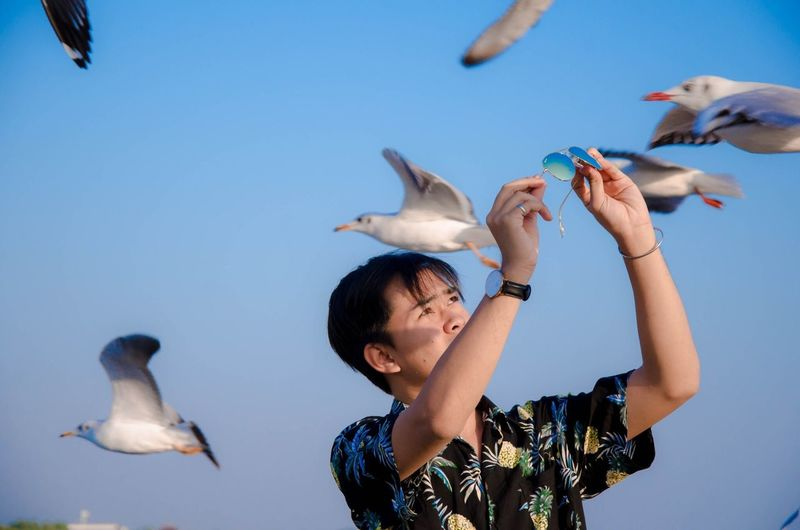 Man holding sunglasses while standing by seagulls flying against sky