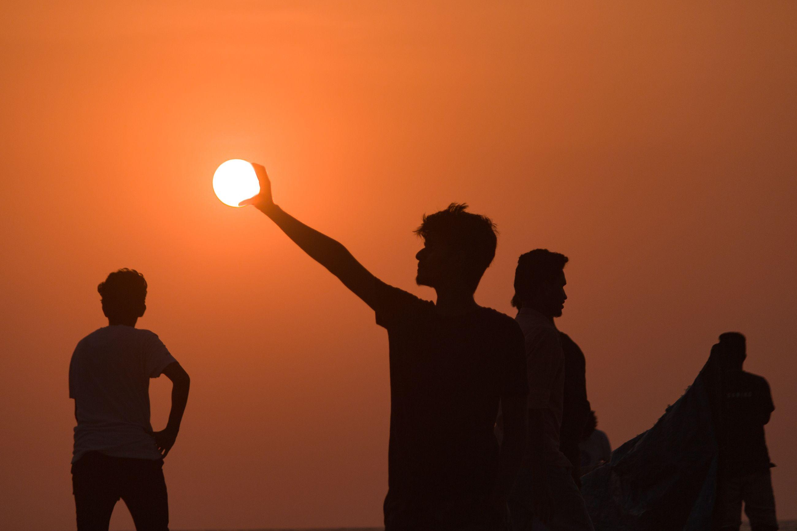 SILHOUETTE FRIENDS STANDING AGAINST ORANGE SKY