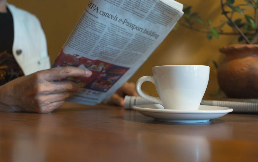 Female reading a news paper with coffee cup on wooden table. Cup Table Mug Drink Coffee Cup One Person Coffee Food And Drink Indoors  Coffee - Drink Refreshment Real People Human Hand Publication Lifestyles Saucer Activity Reading Leisure Activity Book Crockery Hand Tea Cup