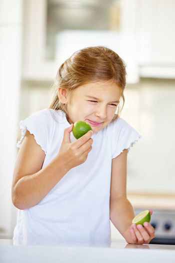 Cute Girl Making Face After Tasting Lime At Home