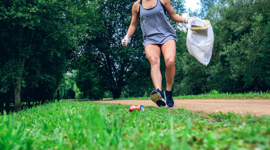 Low section of woman running while holding plastic bag on grass