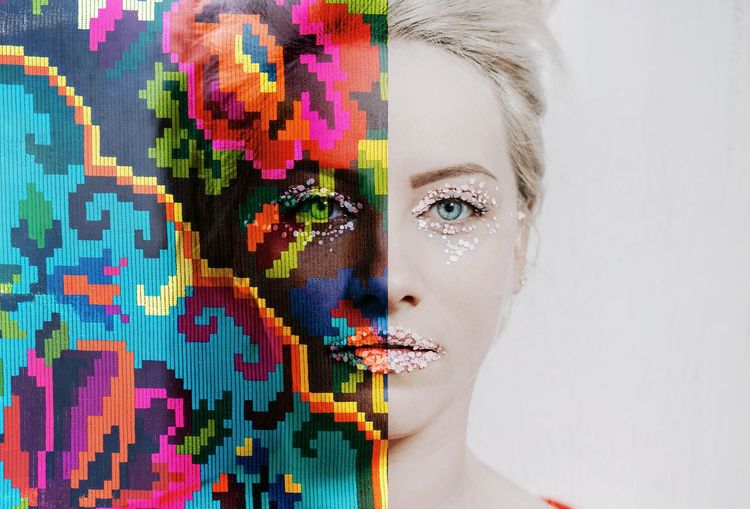 Digital composite image of woman with make-up and colorful pattern against wall