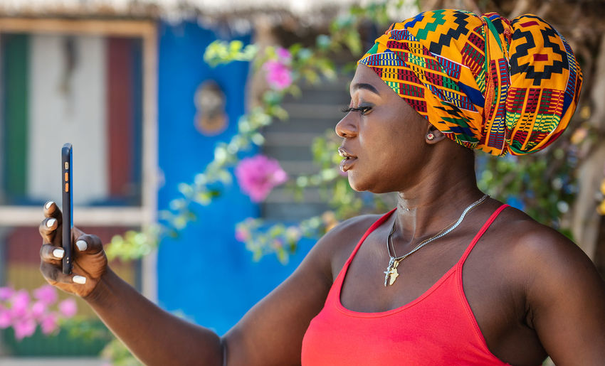 African woman taking selfie picture with colorful traditional african headdress