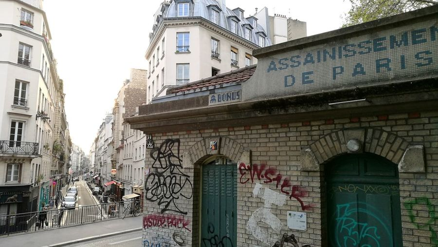 Graffiti on building by street in city