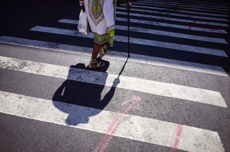 Single person walking across the street zebra while using a cane walking stick in new york city