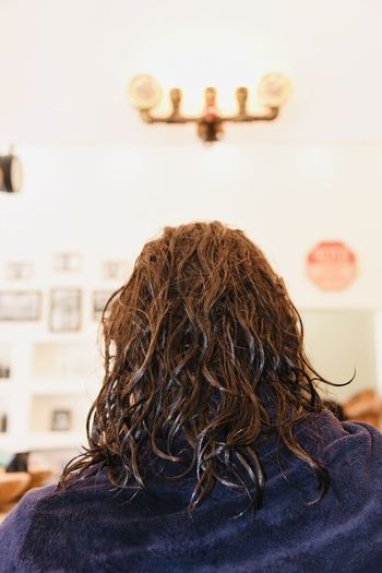 Rear view of man sitting in barber shop