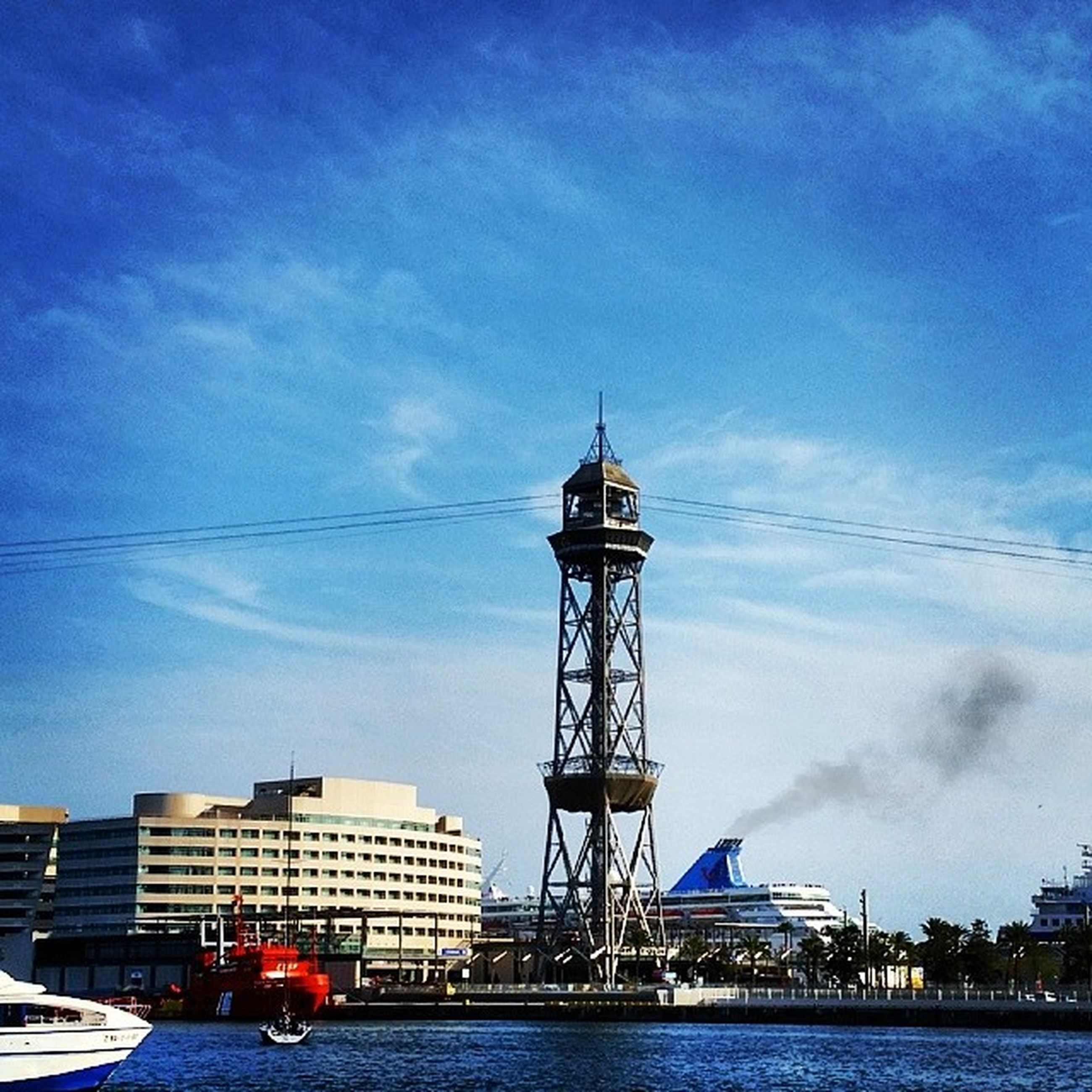 architecture, sky, built structure, building exterior, waterfront, water, cloud - sky, blue, low angle view, nautical vessel, cloud, tower, city, river, tall - high, outdoors, transportation, no people, day, sea