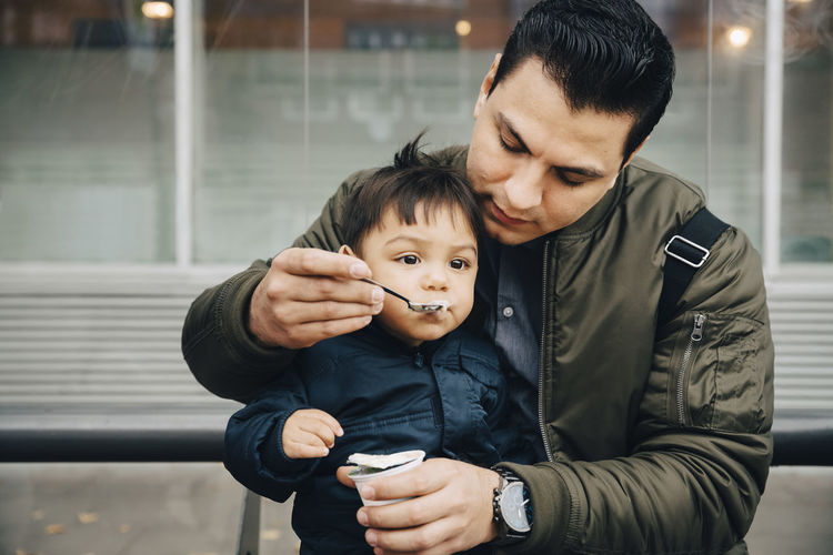 Father and son holding camera