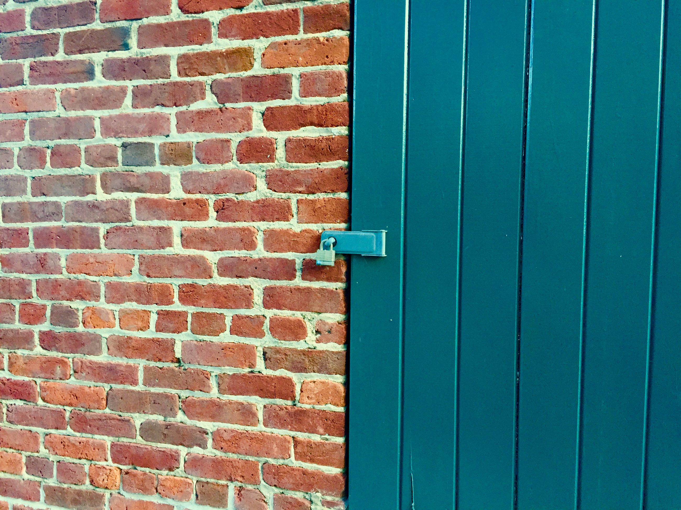 wall - building feature, built structure, architecture, building exterior, brick wall, wall, red, blue, protection, door, safety, closed, day, outdoors, no people, security, textured, pattern, low angle view, close-up