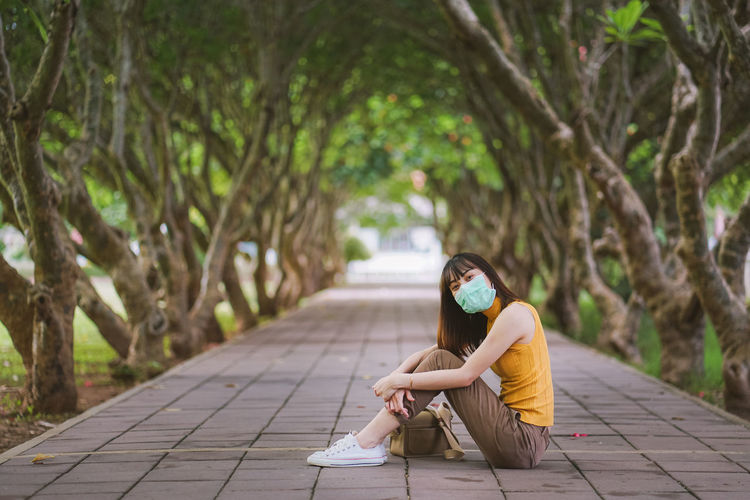 Woman sitting on footpath amidst plants against trees