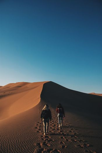 Rear View Of Friends Walking On Desert Against Clear Blue Sky