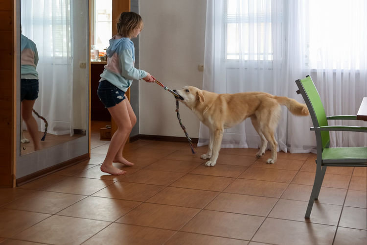 Woman with dog standing on tiled floor at home