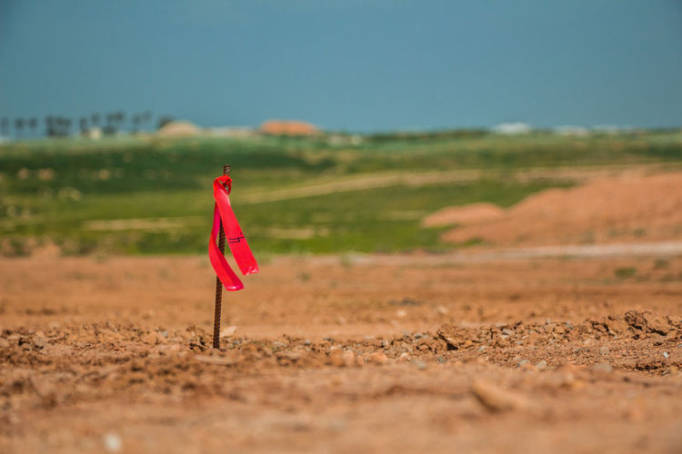 Red flag on field against sky