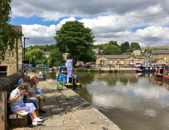 People relaxing on the Leeds Liverpool canal towpath in Skipton, Yorkshire Trip Towpath Boat Canal Yorkshire Leeds Liverpool Canal Barge Transport Peaceful Lifestyle Town Skipton England United Kingdom Cloud - Sky Sky Water Group Of People Real People Incidental People Day Adult Leisure Activity Outdoors Lifestyles Sunlight