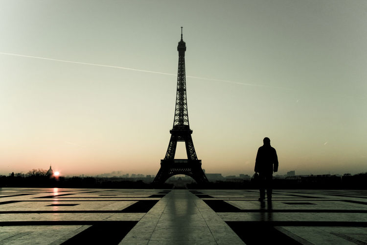 Silhouette man with eiffel tower against sky during sunset