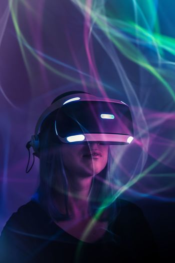 Woman using virtual reality simulator by light paintings