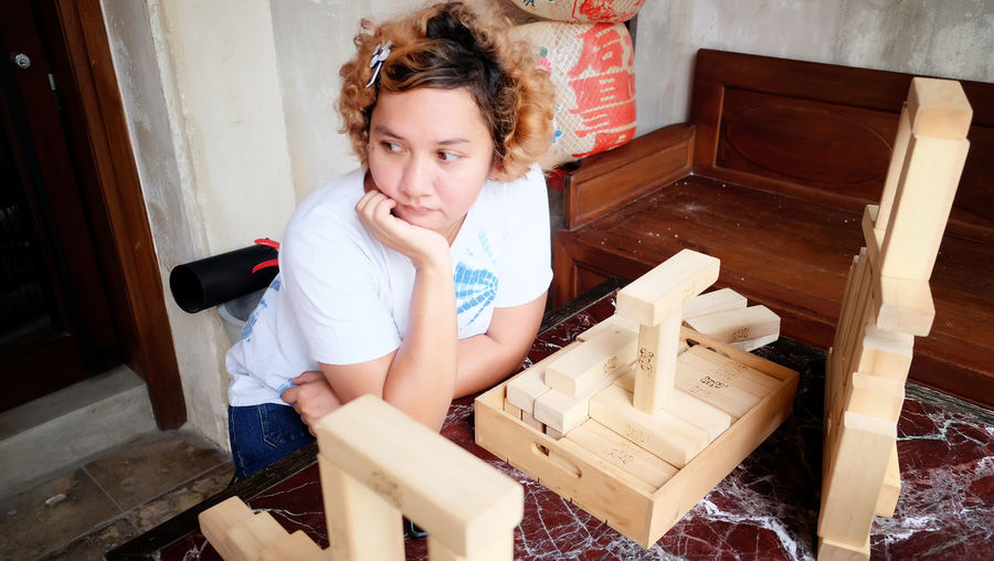 Young Woman Sitting At Table With Wooden Toy Blocks