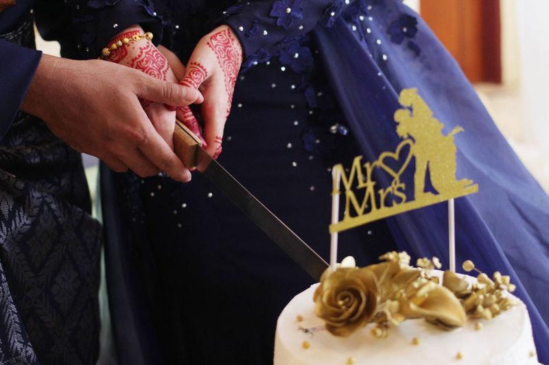 Close-up of bride and bridegroom cutting wedding cake