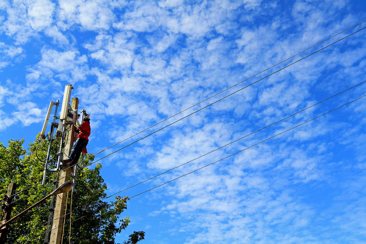 Low angle view of man working against blue sky