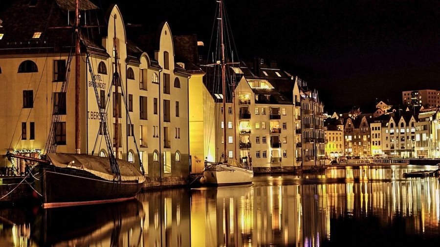 Sailboats moored on canal by illuminated buildings in city at night