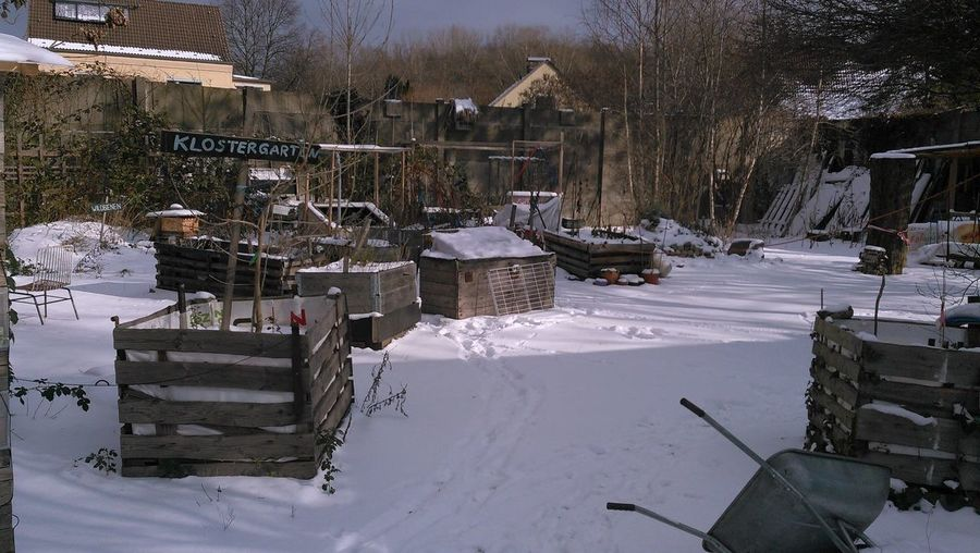 Houses on snow covered field by buildings in city