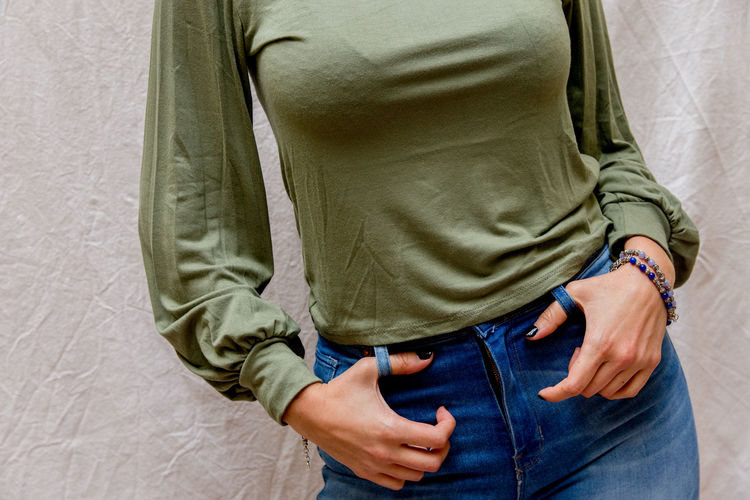 Midsection of woman standing by wall outdoors