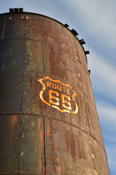 vintage once white Route 66 sign painted on side of old metal railroad water tank, the white sign is now mostly stained orange from the rusting metal Highway Signs Retro Route 66 Mother Road Road Sign Rusty Rusty Metal Rusty Metal Plate Tank Vintage