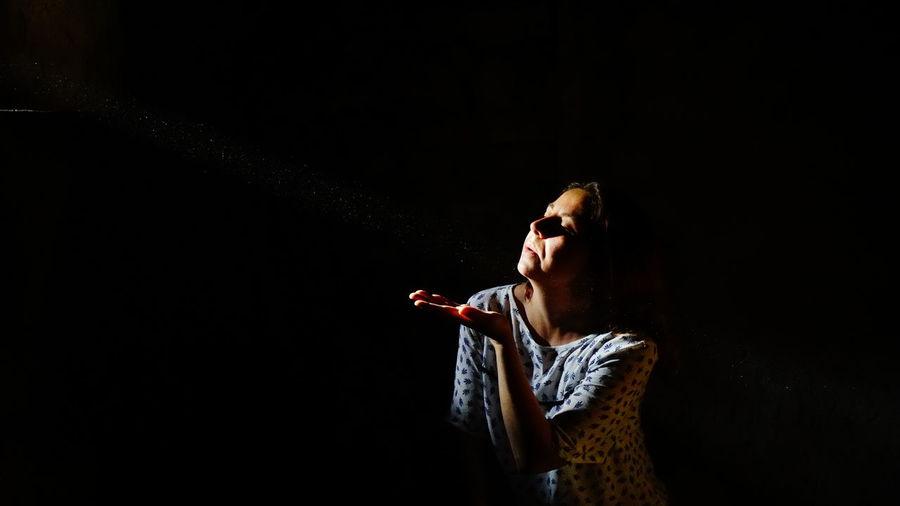 Woman gesturing against black background