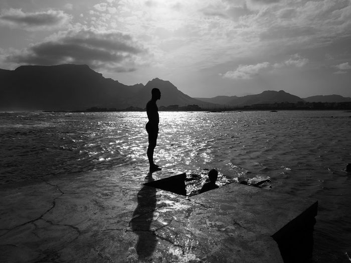 Silhouette Man Standing By Sea Against Sky